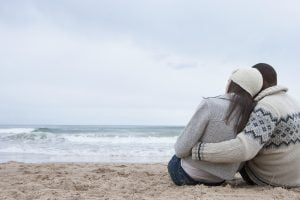 Loving couple sitting and hugging on winter beach from behind